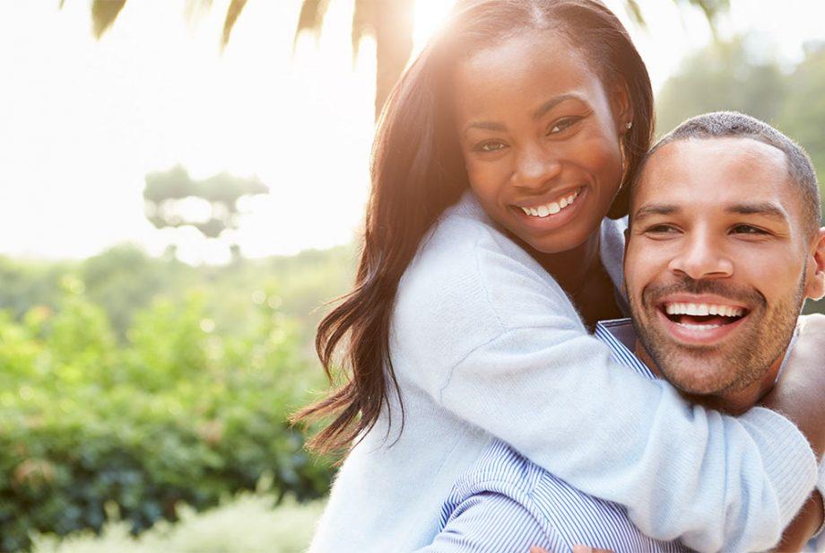 Ein glückliches Paar in Portrait Ansicht, Sie umarmt den Mann von hinten und lachen in die Kamera
