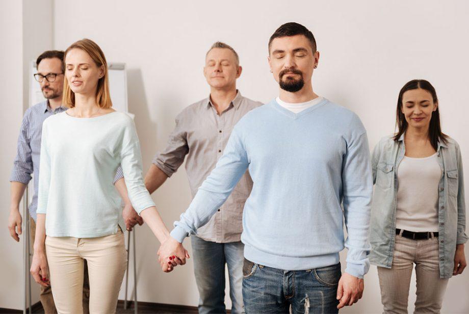Männer und Frauen stehen mit geschlossenen Augen im Raum und spüren ihre Rolle in der Aufstellung